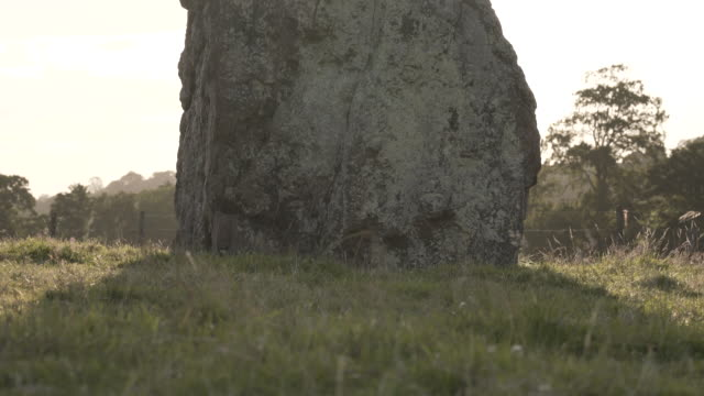 the sun beams from behind the silhouette of a megalith at the stanton drew stone circle on a summer evening - obelisk stock videos & royalty-free footage