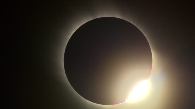 The sun bursts from behind the moon after a total solar eclipse.