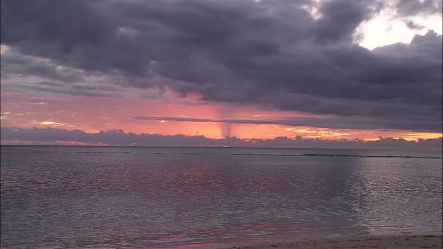 the sun creates a fiery glow when it sets. - seascape stock videos & royalty-free footage