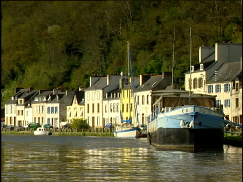 the sun dances on water in the brittany harbour. houses and boats line the waterfront. - ブルターニュ点の映像素材/bロール
