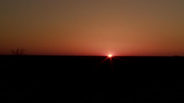 The sun disappears behind a dark, flat horizon.