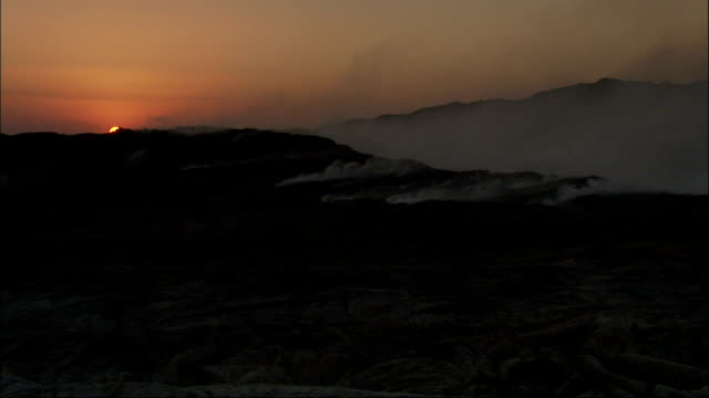 The sun disappears behind a volcanic landscape as smoke pours out of fissures. Available in HD.