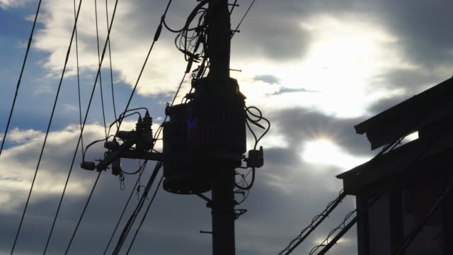 the sun from cloud, which illuminates the utility pole stands in residential area in takada toshima ward tokyo japan on feb. 03 2019. - telephone pole stock videos & royalty-free footage