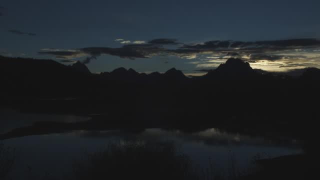 vídeos y material grabado en eventos de stock de the sun glows behind silhouetted mountains near oxbow bend. - río snake