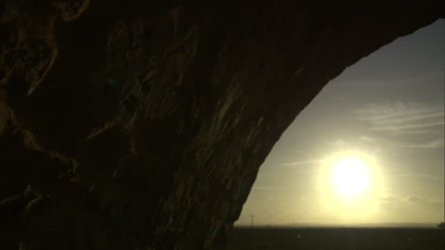the sun glows low on the horizon, shining through an arched opening into a cave. - building entrance stock videos & royalty-free footage