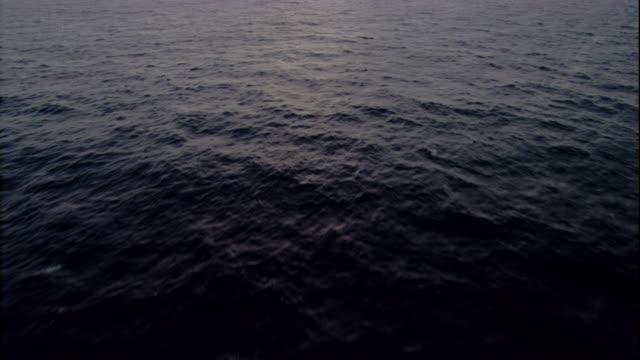 The sun glows on an ocean horizon. Available in HD.