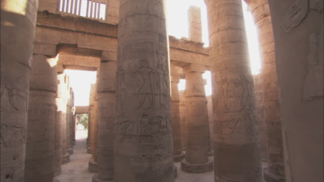 the sun illuminates the interior of an ancient temple in karnak, egypt. - temples of karnak stock videos and b-roll footage