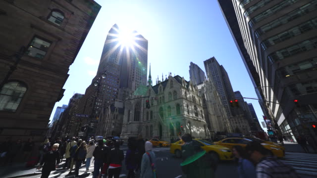 the sun illuminates the people and cars at corner of madison avenue and 51st street among the midtown manhattan skyscrapers - yellow taxi stock videos & royalty-free footage