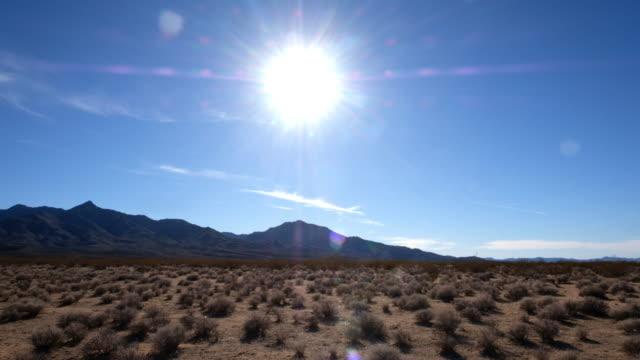 the sun in a desert scene in death valley, california - death valley stock-videos und b-roll-filmmaterial