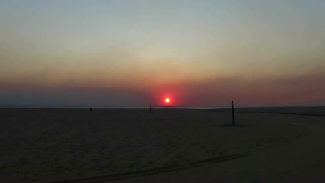 The sun is a bright red from the haze emanating from the Thomas Fire in Ventura California