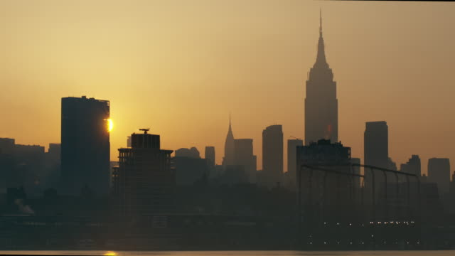 the sun is about the rise over the manhattan skyline early morning.   the empire states building is featured. - 逆光点の映像素材/bロール