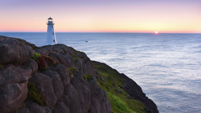 t/l the sun is rising on the lighthouse at cape spear lighthouse national historic site – the most easterly point in north america / cape spear, newfoundland and labrador, canada - leuchtturm stock-videos und b-roll-filmmaterial