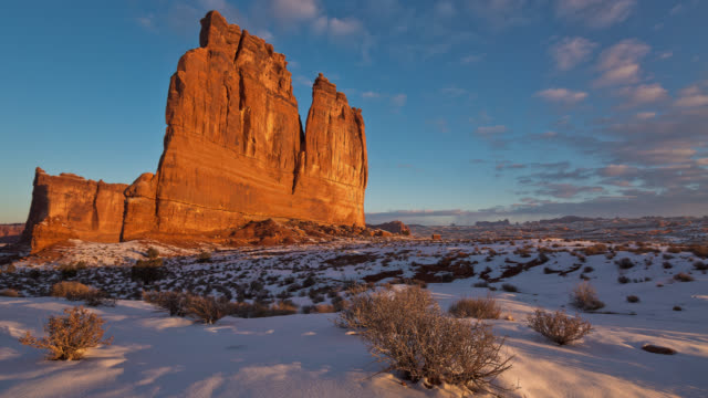 t/l  the sun is rising on the organ sandstone tower in winter / arches national park, utah, usa - sandstone stock videos & royalty-free footage