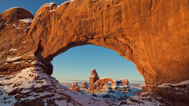 T/L The Sun is rising on Turret Arch and North Window Arch in winter / Arches National Park, Utah, USA