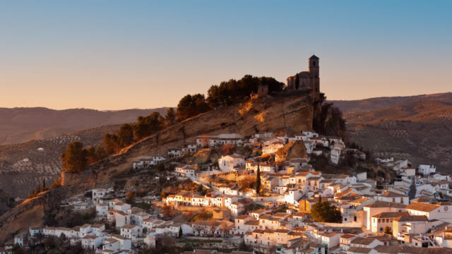 T/L The sun is setting on Montefrio's village and on the ruins of a Moorish castle / Montefrio, Granada, Spain