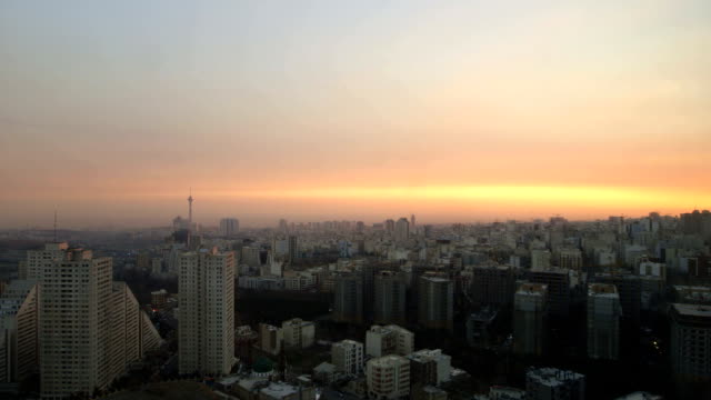 the sun is setting over tehran city and the milad tower - tehran stock videos and b-roll footage