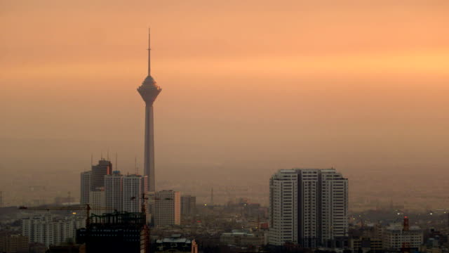 the sun is setting over tehran city and the milad tower - iran stock videos and b-roll footage