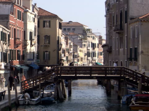 the sun lights the buildings and streets of venice as pedestrians cross a bridge. - italy stock videos & royalty-free footage