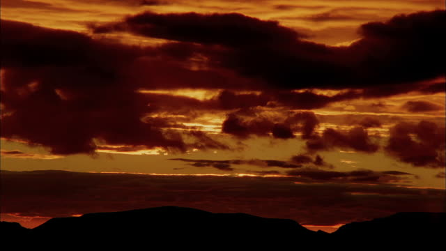 the sun moves through silhouetted clouds above the desert and mountains in arizona. - südwestliche bundesstaaten der usa stock-videos und b-roll-filmmaterial