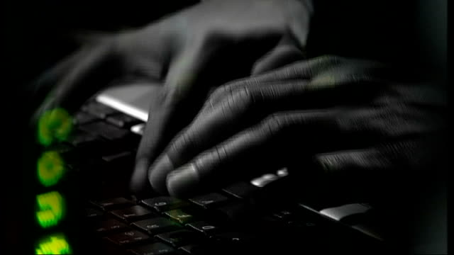 'the sun' newspaper website hacked and personal data stolen t26061124 orig r05120705 shots of anonymous man using laptop computer in darkened room... - channel 4 news stock-videos und b-roll-filmmaterial