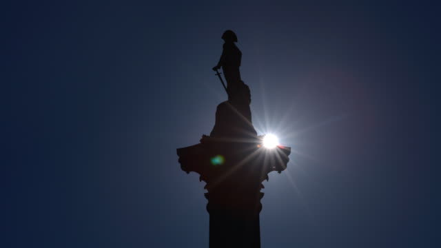 The sun passes behind Nelsons column silhouetting the statue before it reappears on the other side