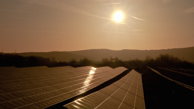 vídeos de stock e filmes b-roll de the sun passes over photovoltaic panels in saarland, germany. - painel solar
