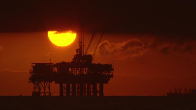 太陽は、前景のオフショア石油掘削リグプラットフォームのシルエットと劇的な嵐の空の下の日没時に背景に石油(石油)タンカーと嵐雲の下から覗きます - 気候変動点の映像素材/bロール