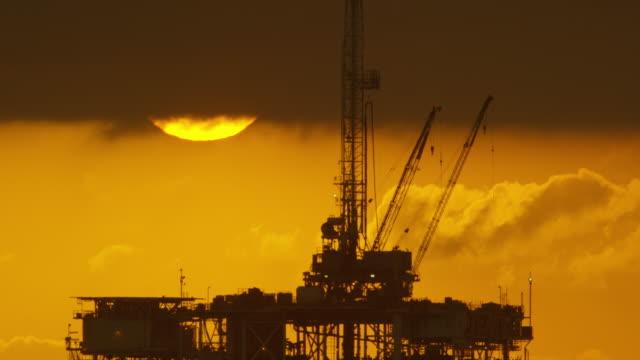 vídeos de stock, filmes e b-roll de o sol espreita por baixo das nuvens de tempestade com uma silhueta de uma plataforma de perfuração de petróleo offshore no primeiro plano ao pôr do sol um céu dramático e tempestuoso - equipamento
