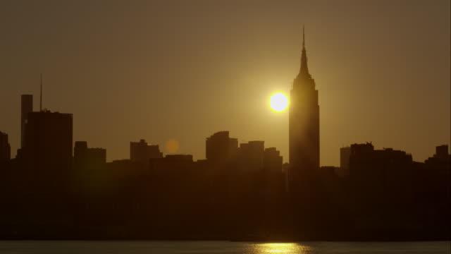 The sun peeks over the Midtown skyline of Manhattan at sunrise.