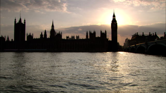 the sun reflects off the thames river and silhouettes the palace of westminster and big ben in london, england. - clock tower stock videos & royalty-free footage