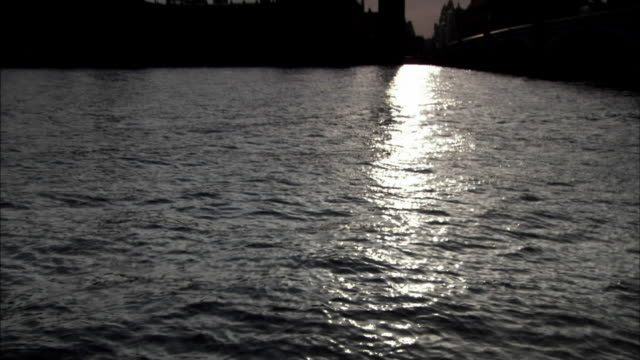 the sun reflects off the thames river near the houses of parliament in london, england. - house of commons stock videos & royalty-free footage