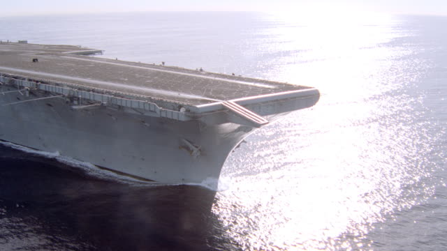 vidéos et rushes de the sun reflects off the water as an aircraft carrier travels over the ocean. - aller tranquillement