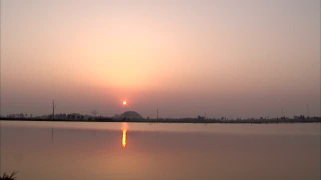 the sun reflects on a lake at golden hour. - tay ninh stock videos & royalty-free footage