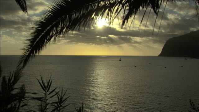 vídeos de stock e filmes b-roll de the sun reflects on the ocean at golden hour. - penhasco caraterísticas do território