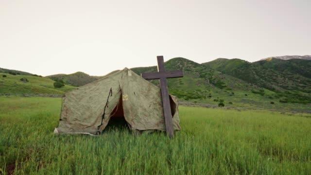die sonne hinter eine christian tent-kapelle, in einem feld für cowboys zu besuchen - utah stock-videos und b-roll-filmmaterial