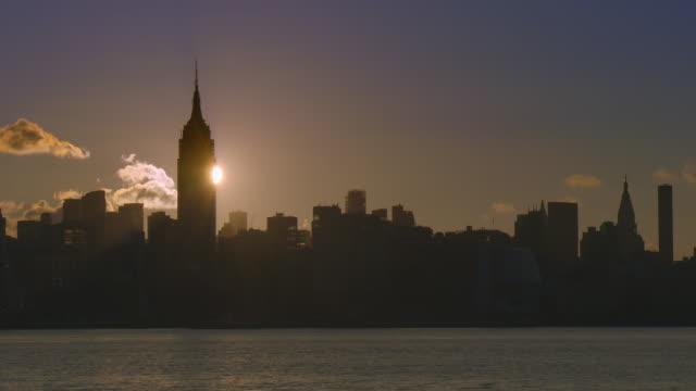 vídeos y material grabado en eventos de stock de the sun rises behind a silhouetted new york skyline at dawn. - empire state building