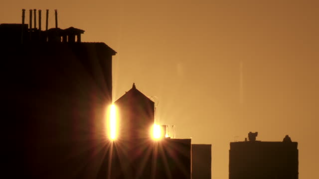 The sun rises behind buidlings that are in silouette