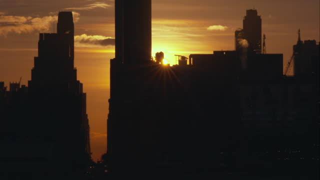 the sun rises behind skyscrapers and buildings in manhattan. - overcast stock videos & royalty-free footage