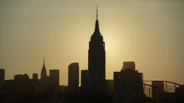 The sun rises behind the Empire State Building early morning.  The skyline is in silhouette