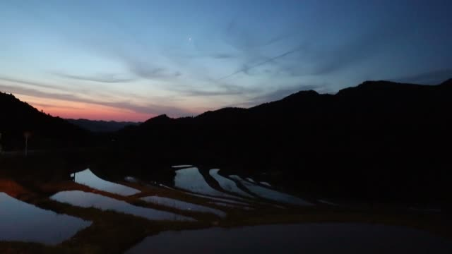 The sun rises behind the Oyama Senmaida terraced rice fields in Kamogawa Chiba Japan on Wednesday May 3 2017 Shots wide shot of reflecting paddy...
