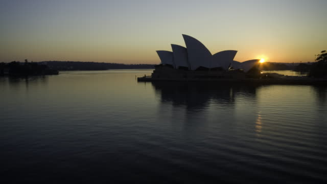 the sun rises behind the sydney opera house - オペラ座点の映像素材/bロール