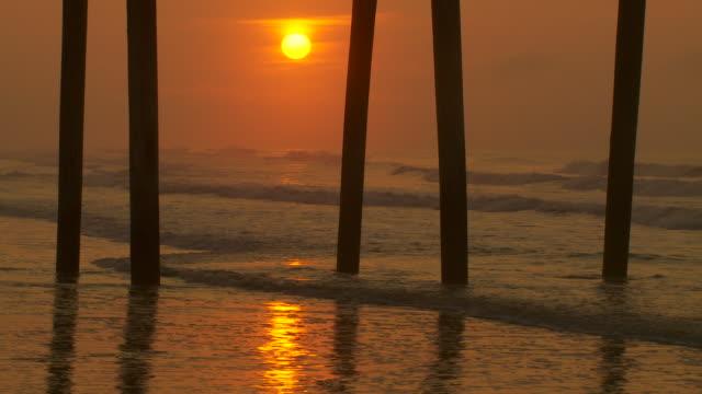 vídeos y material grabado en eventos de stock de cu of the sun rises beneath a wooden pier in ocean city nj.  waves break under the pier and the sky is a copper orange. - orange nueva jersey
