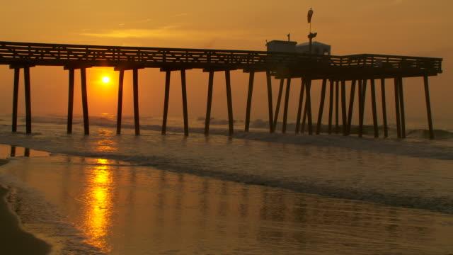 vídeos y material grabado en eventos de stock de the sun rises beneath a wooden pier in ocean city nj.  waves break under the pier and the sky is a copper orange. - orange nueva jersey