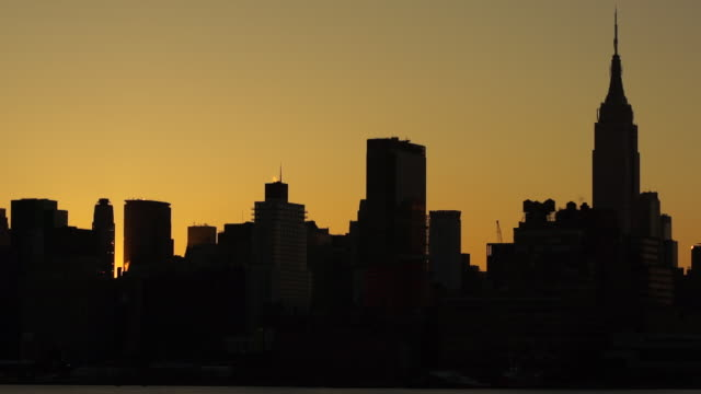 The sun rises between businesses and apartment buildings in the city.  Time Lapse