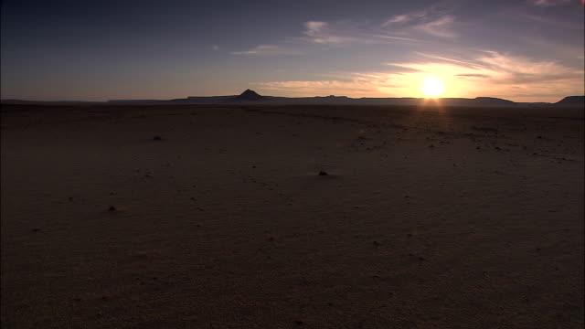 the sun rises on the horizon in a barren area of the sahara desert. - sahara desert stock videos & royalty-free footage