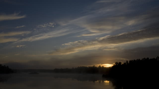 The sun rises over a misty river by a forest.