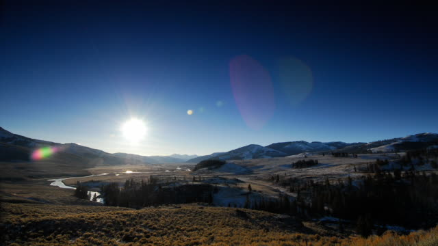 The sun rises over a valley surrounded by mountains in Yellowstone National Park.