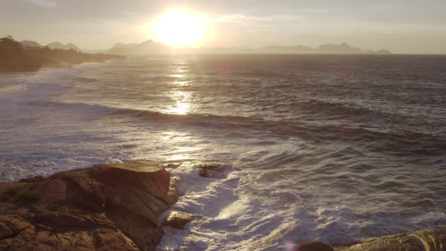 the sun rises over frothy waves at ipanema beach in rio de janeiro - riva dell'acqua video stock e b–roll