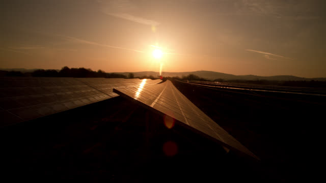 The sun rises over photovoltaic panels in Saarland, Germany.