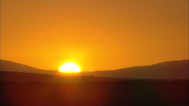 the sun rises over silhouetted mountains on the horizon. - western cape province stock videos & royalty-free footage
